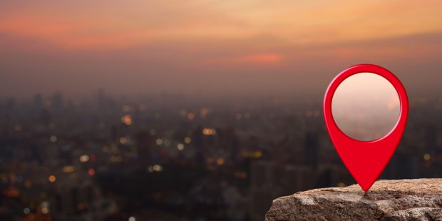 Red location icon on a rock overlooking a city at dusk